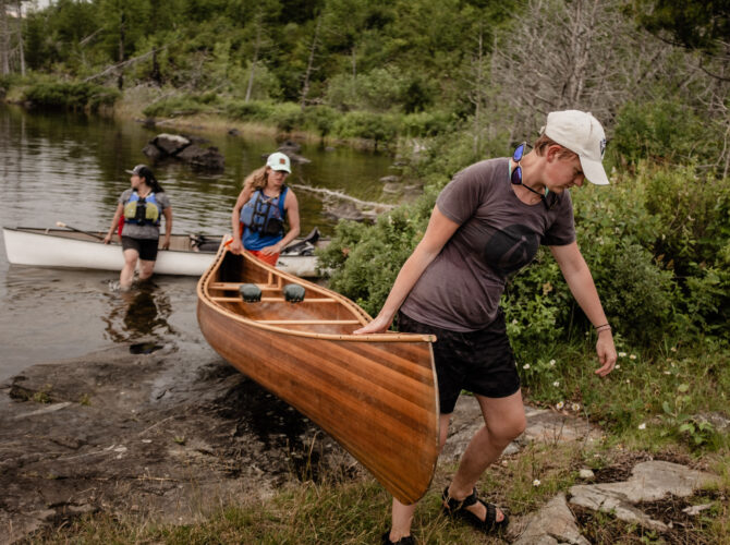 Paddlers lifting a canoe out of the water in the BWCA