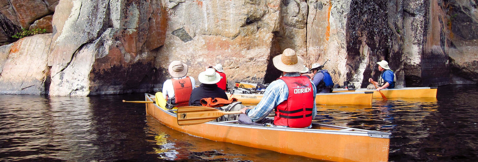 Canoes gathering by a rock face in the BWCA
