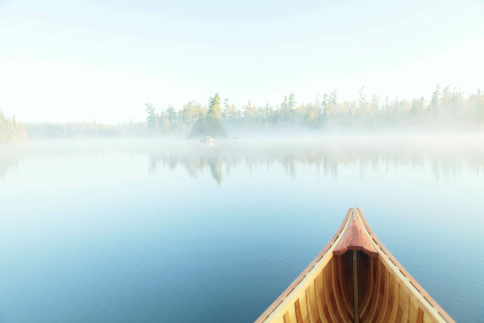Canoe in water with fog on top of the water