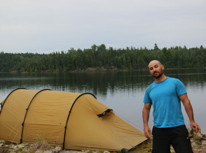 Man pictured with camping tent and various gear related items