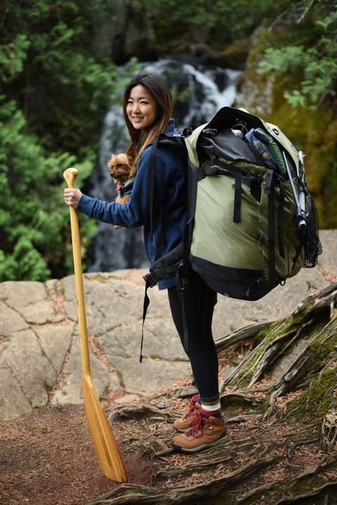 Friends of the Boundary Waters explaining how to pack for a trip to the Boundary. Image of a woman with her backpack on exploring the Boundary Waters