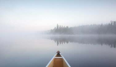 Bow of a canoe on a misty lake in the Boundary Waters