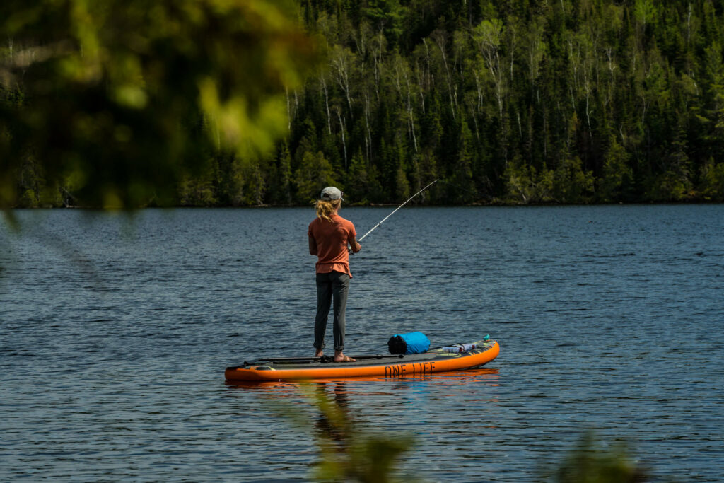 A woman fishes while standing on her stand up paddle board.