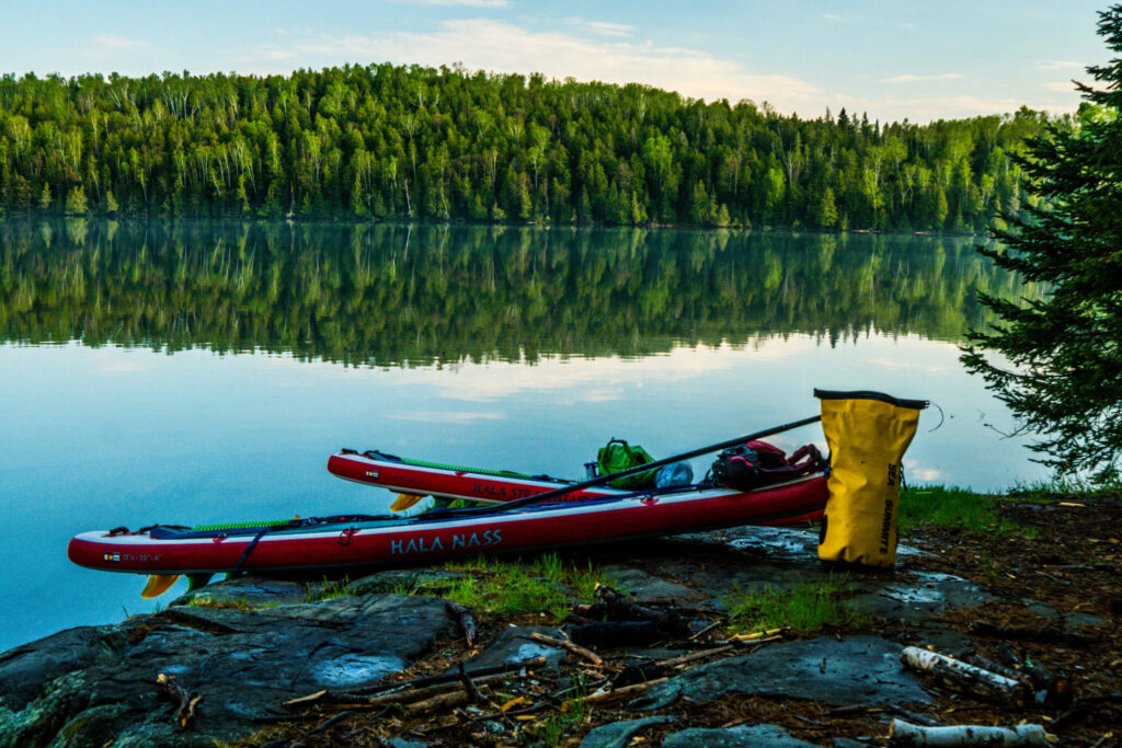Image of two stand up paddle boards resting on the shores of the Boundary Waters.