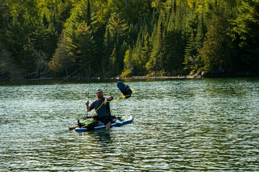 Image of a man sitting on his stand up paddle board while fishing.