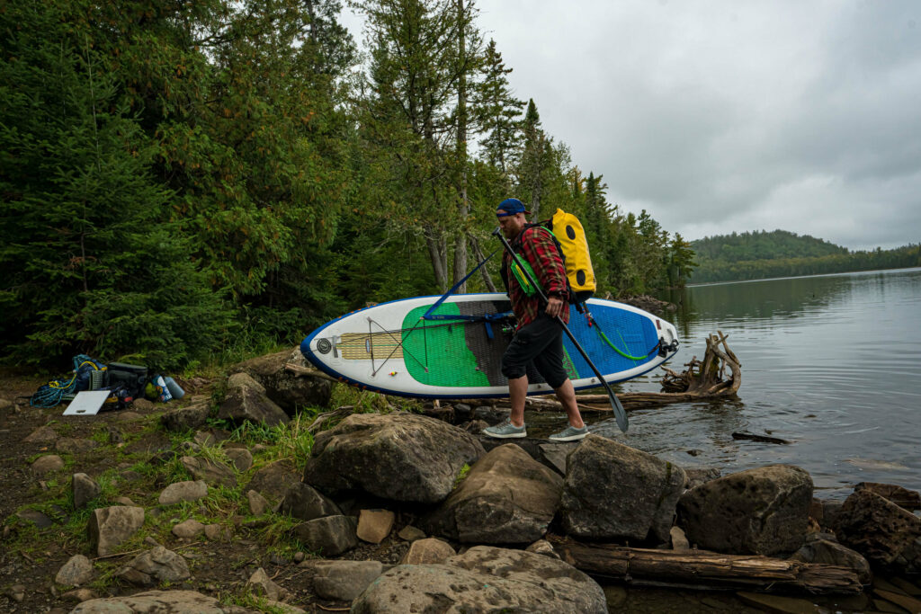 Image of a man portaging his stand up paddle board in Boundary Waters