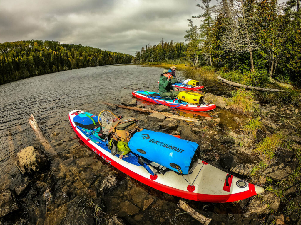 A group of explorers stop for a break after paddle boarding the Boundary Waters.