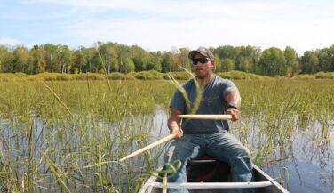Darin Powell beats rice kernel into the hull of his canoe.