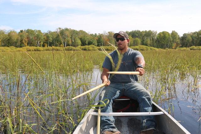 Darin Powell beats rice kernel into the hull of his canoe