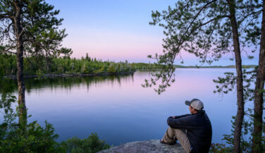 Man looking over a lake from a campsite in the Boundary Waters.