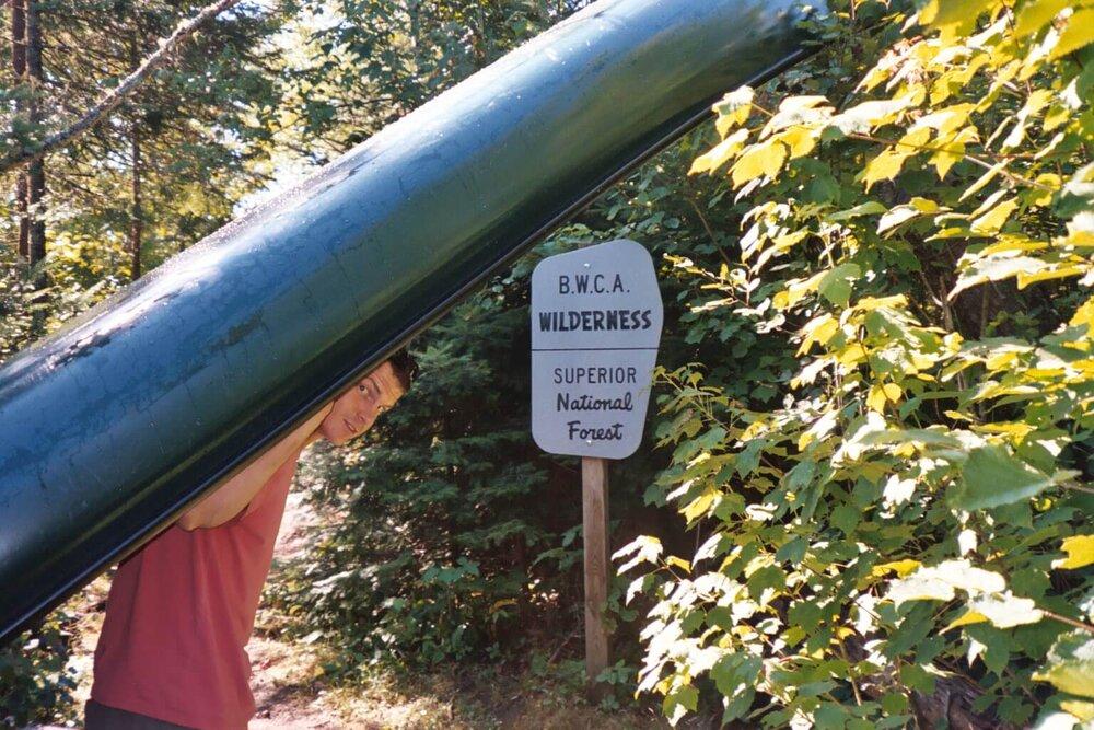 Man portaging a canoe in the BWCA Wilderness