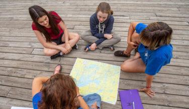 Tweens sitting around a map of the BWCA
