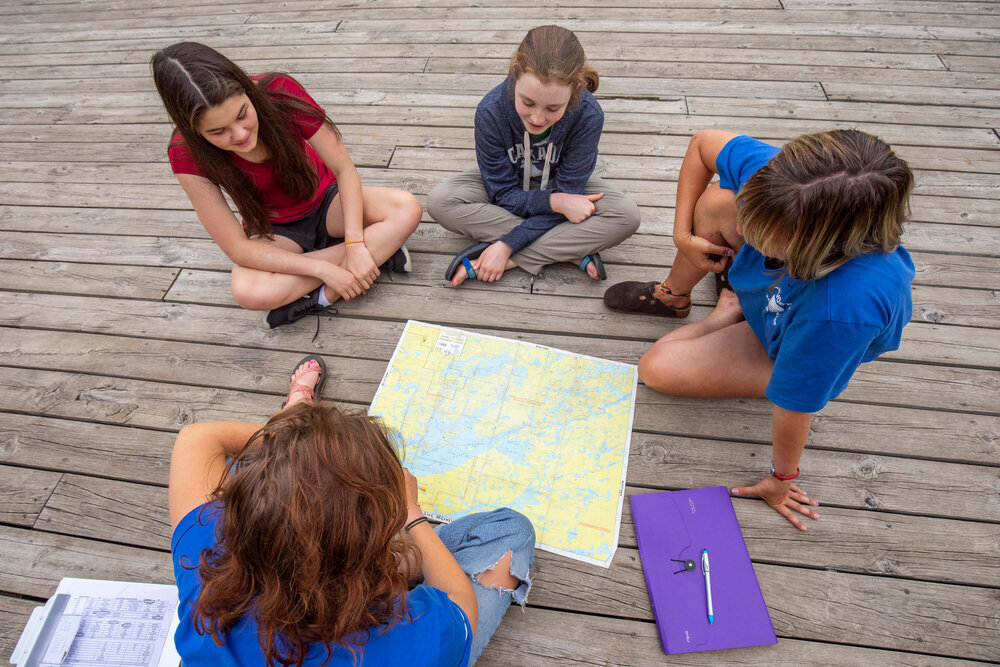 Tweens studying a map of the Boundary Waters