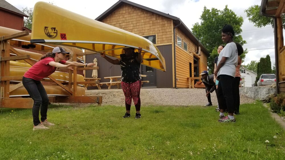 Woman practicing portaging a canoe at an outfitter.