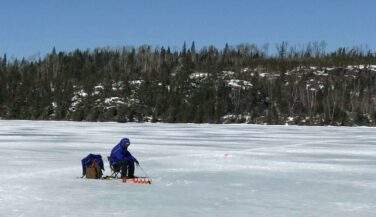 Man ice fishing in the middle of an icy lake.
