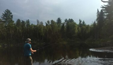 Man fishing from the shore in the BWCA