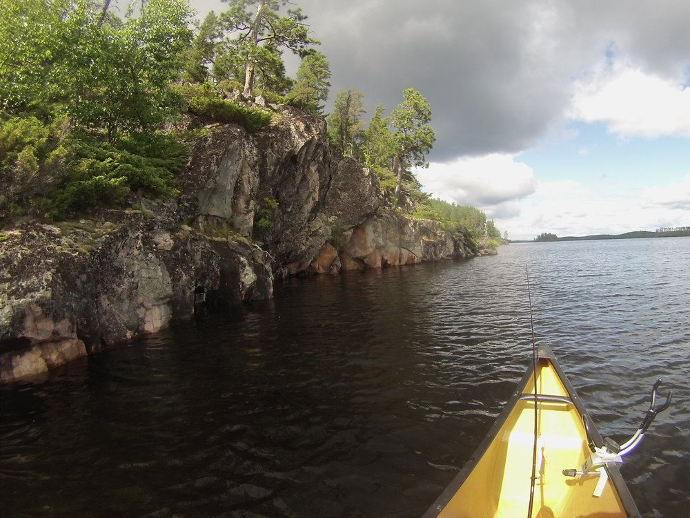 Canoe with fishing pole next to a steep rock face