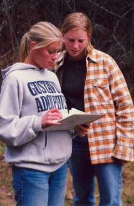 Two women looking at paperwork while at the Boundary Waters